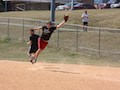 Softball Against Humanity first baseman leaps to prevent an overthrow against the Bones Brigade.